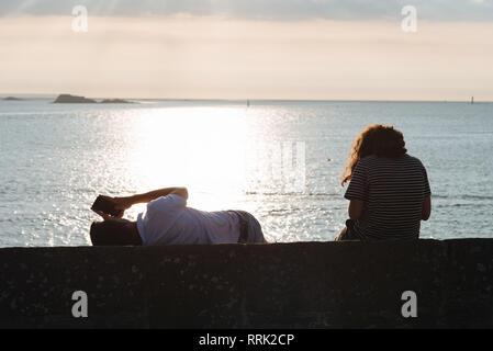 Ansicht der Rückseite des paar Aprilscherze sitzend an der Wand bei Sonnenuntergang gegen Ozean - Stockfoto