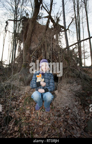 Das Mädchen in einem Wald, mit einem stofftier. Das Kind erhielt im Wald verloren. - Stockfoto
