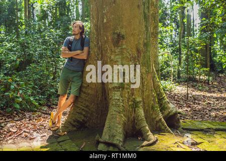 Ein Mann in der Nähe von einem großen Baum. Die Wurzeln eines alten Baumes, Bali. Reiseziel der Insel Bali, der Kultur, der Kunst, des indonesischen Volkes - Stockfoto