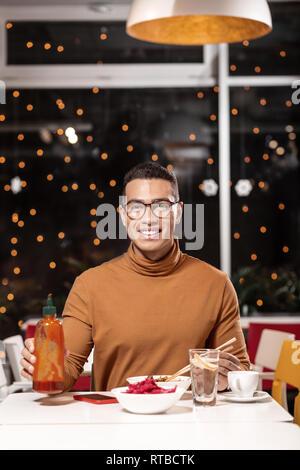 Vertikale Portrait von Kerl, dem die Kellner bringen köstliches Drei-Gang-Menü, während er die Flasche. - Stockfoto