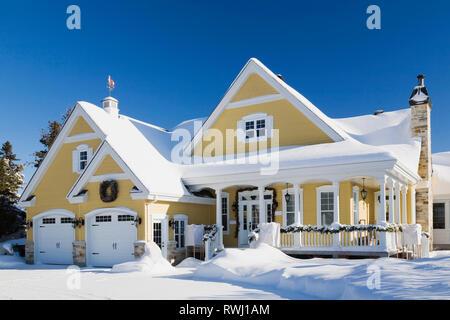 Gelb mit weißen Zierleisten Landhausstil Hausfassade mit Weihnachtsschmuck im Winter, Quebec, Kanada - Stockfoto