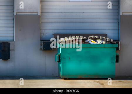 Lager Außenwand mit Garagentor und Müllcontainer bei Tageslicht - Stockfoto