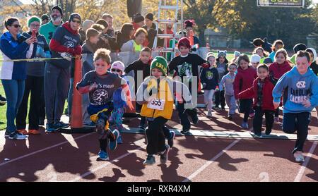 West Islip, New York, USA - 24. November 2017: Beginn der Kinder laufen auf einer roten Piste mit ihren Eltern sie jubelnd an einem lokalen türkei Trab Rennen o - Stockfoto