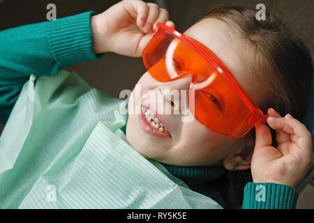 Kleines Mädchen sitzt in der zahnmedizinischen Stuhl und trägt eine Schutzbrille. Sie Plantscht. - Stockfoto