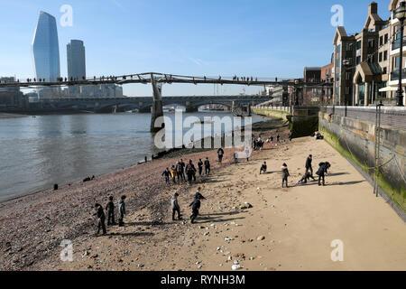 Ein Blick auf die schulkinder Schule Gruppe mudlarking auf der nördlichen Sandstrand Seite der Themse im Winter sunshine London England UK KATHY DEWITT - Stockfoto