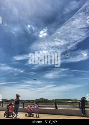 Eine Frau schiebt einen Kinderwagen neben einem kleinen Kind, das auch einen Kinderwagen entlang der Strandpromenade - Stockfoto