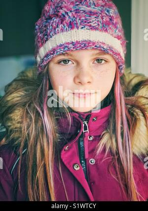 Portrait eines Mädchens mit lila Haaren streifen tragen lila Winter Mantel und Hut - Stockfoto