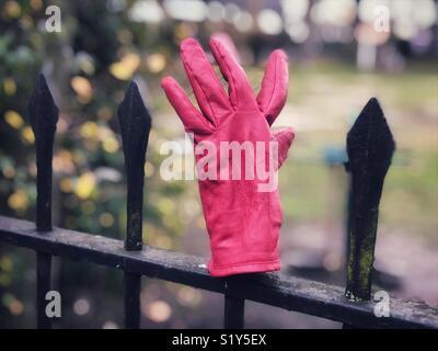 Ein Handschuh hinter sich gelassen auf diesen Park Geländer, Aufnahme, wie sie sind. - Stockfoto