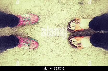 2 Paar Schuhe, Sandalen und Trainer tragen - Stockfoto