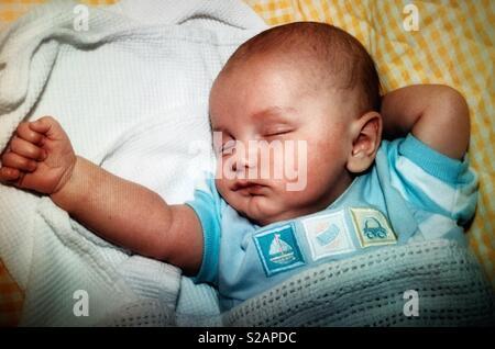 Ein Baby schläft mit seinem Arm ausgefahren - Stockfoto