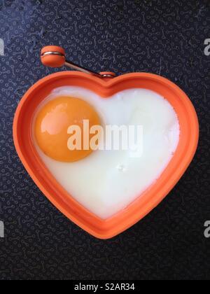 Spiegeleier, gebratenen Braten in der Pfanne. Die Eier ist in der Form eines gesunden Herzens eine gesunde Ernährung und gutes Wohlbefinden zu implizieren. - Stockfoto