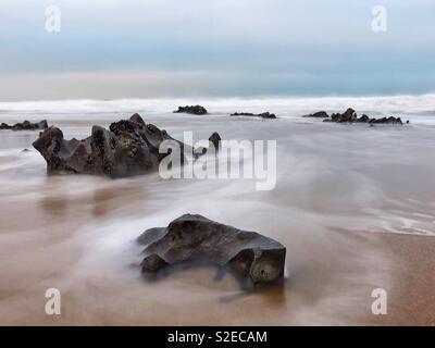 Eingehende morgen Tide waschen um Felsen auf ein Waliser Surf Beach bei rauem Wetter, November. - Stockfoto