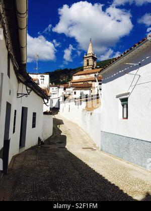Suchen nach einem schmalen Weg oder die Straße in einem Dorf in Andalusien Spanien durch die alte weiße Häuser und Kirche auf dem Hügel - Stockfoto