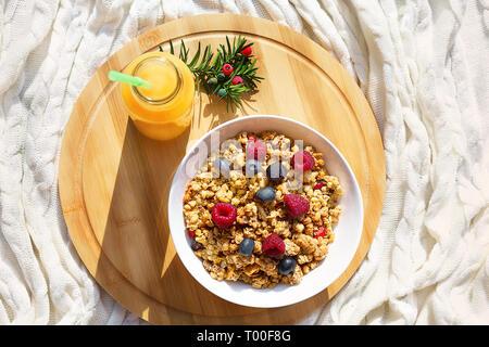 Ansicht von oben auf ein gesundes Frühstück mit Müsli und Beeren Himbeere, Heidelbeere in weiße Schüssel und frischen Orange juce auf runden Holz- Fach auf gemütlichen gestrickt, w - Stockfoto