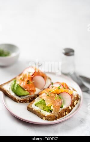 Toast mit Avocado, Gurke und Lachs auf hellen Hintergrund. Gesundes Frühstück Konzept - Stockfoto