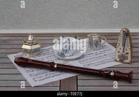 Englisch Teetasse mit Untertasse, creme Kanne, Sugar Bowl und Zucker Löffel, mit floralem Dekor und Metronom für Musik und einen Block Flöte auf einem Blatt von Musik - Stockfoto