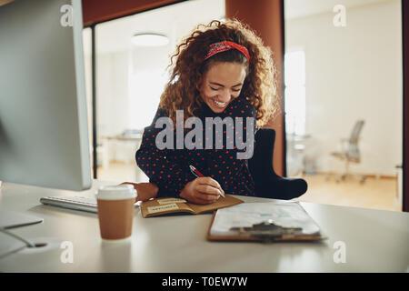 Lachende junge geschäftsfrau an ihrem Schreibtisch sitzen in einem Büro das Schreiben von Notizen und Arbeiten auf einem Computer - Stockfoto