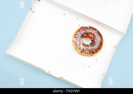 Letzte Schokolade Donut in leeren Kasten auf Pastell-blaue Hintergrund - Stockfoto