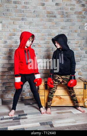 Wenig Zwillingsbrüder Dressing in Sportswear Boxhandschuh in einem Studio posieren. - Stockfoto