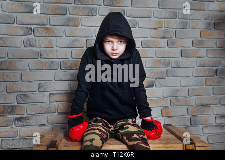 Kleiner Junge Boxer mit blonden Haaren Dressing in schwarz sweatshirt Boxhandschuh in einem Studio posieren. - Stockfoto