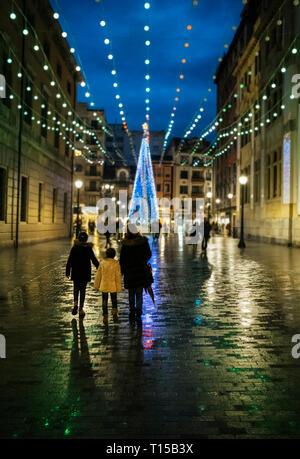 Spanien, Gijon, Rückansicht von Mutter und zwei Kinder wandern in der Fußgängerzone in den Abend in der Weihnachtszeit - Stockfoto