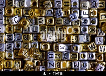 Gold und Silber Würfel mit schwarzen englischen Buchstaben. - Stockfoto
