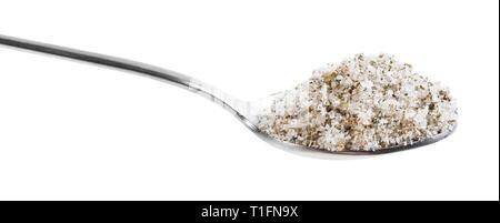Seitenansicht von Stahl Teelöffel mit Salz gewürzt mit Gewürzen und getrockneten Kräutern schließen bis auf weißem Hintergrund - Stockfoto