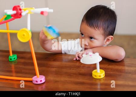 Moody's Kind allein Spielen mit Lernen Spielzeug auf dem Tisch und das Ausdrücken von Anti soziales Verhalten. - Stockfoto