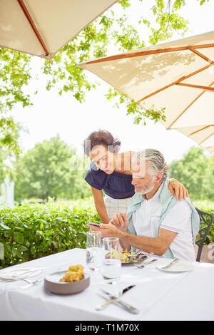 Älteres Ehepaar mit Smart Phone im Patio Restaurant - Stockfoto