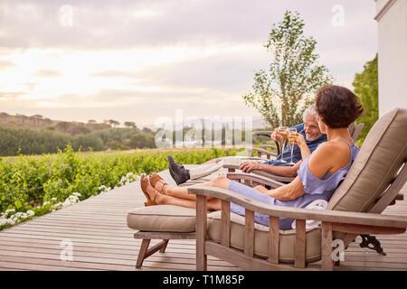 Reifes Paar toasten Champagnergläser auf Hotel Patio - Stockfoto