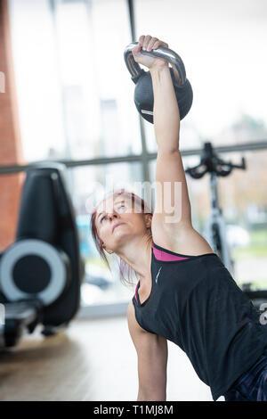 Eine Frau führt die Türkische getup mit einer kettlebell in einer Turnhalle UK - Stockfoto