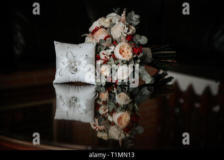 Brautstrauß und Trauringe auf weißen Hintergrund. Reflexionen. - Stockfoto
