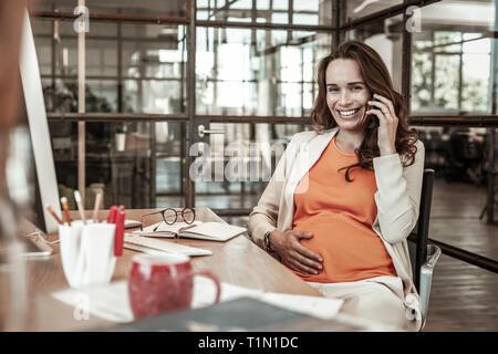 Ansprechende hart arbeitende Frau mit breiten Grinsen, während im Gespräch - Stockfoto
