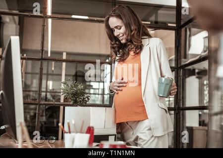 Fröhliche Zukunft Mutter halten Ihren schwangeren Bauch beim Befüllen, - Stockfoto