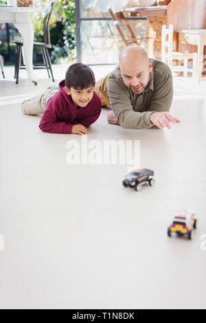 Vater und Sohn spielen mit Spielzeug Autos auf dem Boden - Stockfoto
