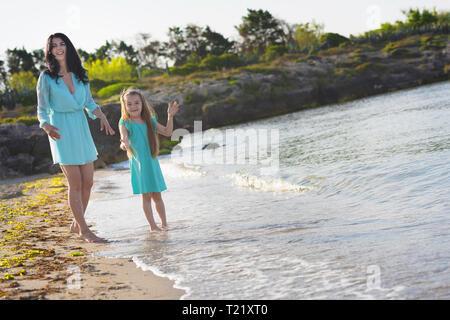 Glücklich liebende Familie Mutter und Tochter Spaß am Strand bei Sonnenuntergang - Mom das Spielen mit Ihrem Kind siehe nächsten im Urlaub - Elternteil, Urlaub, Familie l - Stockfoto