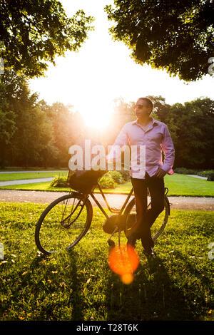 Mann stand in der Nähe von Fahrrad mit Picknickkorb auf es - Stockfoto