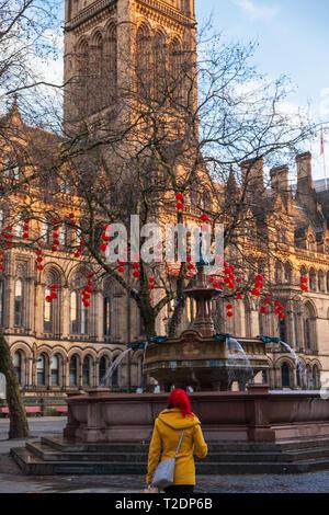 Manchester, Großbritannien - 17 Februar, 2019: rothaarige Frau geht vor dem Rathaus von Manchester in roten chinesischen Neue Jahr Laternen dekoriert - Stockfoto
