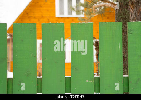 Gelbes Haus hinter dem Grün Holzzaun, Outdoor 7/8 Shot - Stockfoto