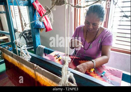 Ein Nepali Frau sticken Seide und Wolle pashmina Schals von Webstuhl, W.F. Nepal, eine nichtstaatliche Organisation, die Beschäftigung von marginalisierten Frauen auf einer gleichberechtigten Basis. - Stockfoto