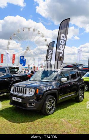 Sonnigen Tag für Leute an der glänzenden schwarzen Jeep Renegade (kleine SUV-Auto) über den Handel stand by - Geparkte große Yorkshire zeigen, Harrogate, England, Grossbritannien Suche - Stockfoto