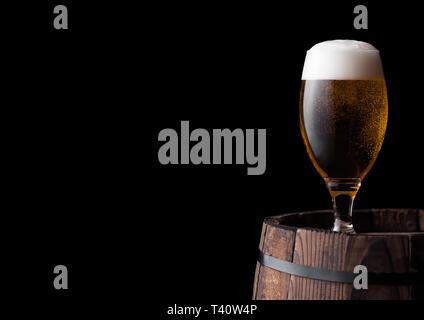 Kalten Glas Handwerk Bier auf alten Holzfass auf schwarzem Hintergrund - Stockfoto