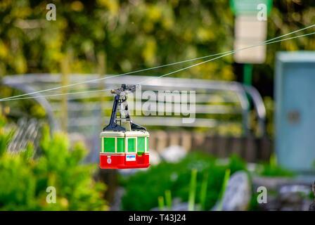 Eine Seilbahn von der Modelleisenbahn auf der Insel Mainau im Bodensee, Deutschland, fließt durch das Bild. - Stockfoto