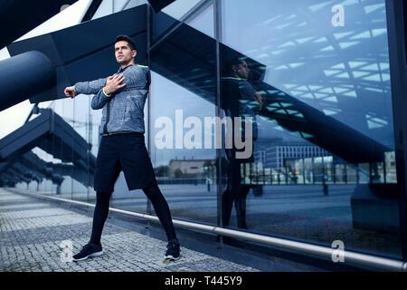 Aktiver Mann seine stretching Training tun Neben moderner Architektur mit Glaswand. Städtischer Bereich Landschaft. - Stockfoto