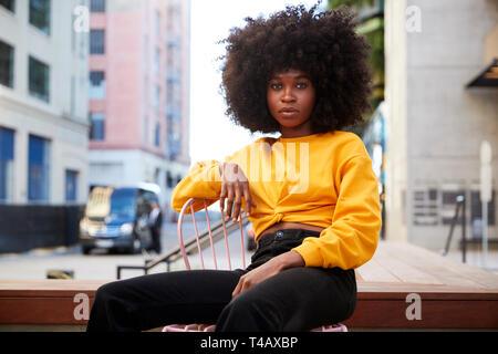 Junge schwarze Frau mit afro Haar und gelb Top sitzt auf einem Stuhl in der Straße an der Kamera auf der Suche - Stockfoto