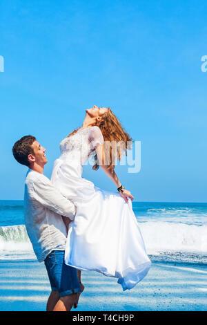 Happy Family auf Hochzeitsreise holiday - Just married junger Mann und Frau viel Spaß auf schwarzem Sand Strand. Aktiver Lebensstil, Menschen Aktivität im Freien im Sommer - Stockfoto