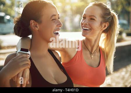 Zwei passen junge Frauen in Sportkleidung lachend, während draußen stehen Arm in Arm an einem sonnigen Tag vor einem Lauf zusammen - Stockfoto