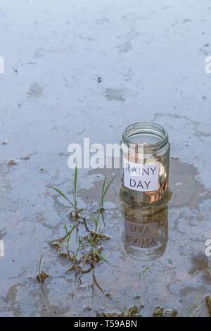 Geld jar/regnerischen Tag Einsparungen jar im Freien bei Sonnenschein. Metapher persönlichen Ersparnissen, Geld sparen, Pensionsvorsorge, Sparen für den Ruhestand. - Stockfoto