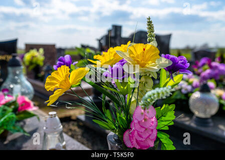 Künstliche Blumen und Kerzen liegen auf dem Grabstein auf dem Friedhof. - Stockfoto