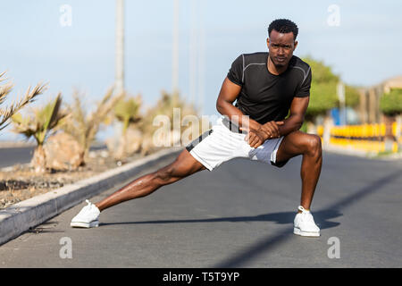 Schwarzen afrikanischen amerikanischen Jungen Mann dehnen sich, nachdem im Freien joggen - Stockfoto